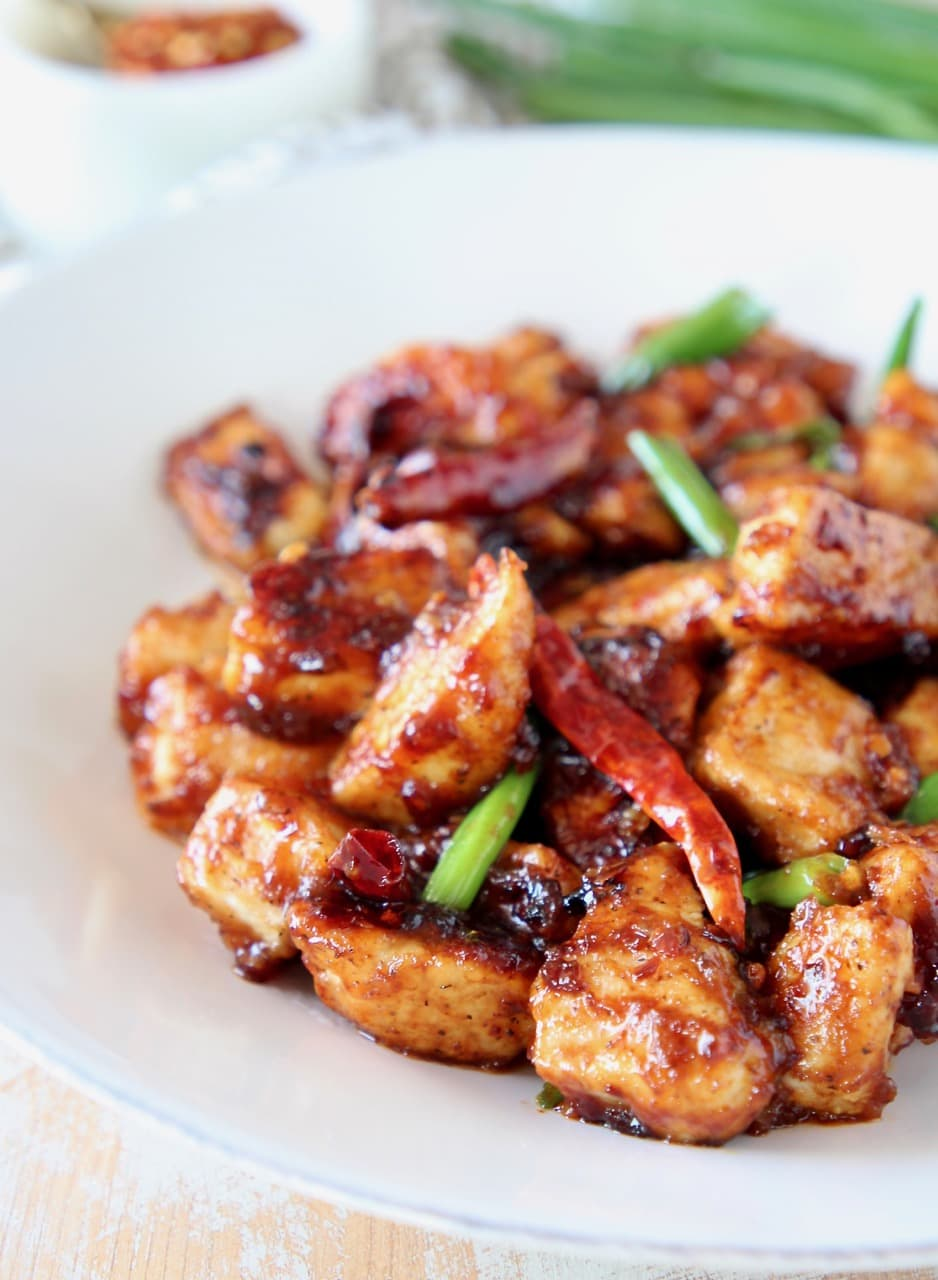 General tso chicken on plate with red chilies and scallions