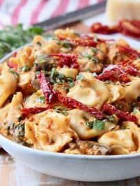 Vegetarian tortellini in white bowl with sun dried tomatoes, mushrooms and basil