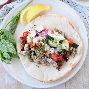 Greek gyro in pita bread on plate with lemon wedges and fresh mint