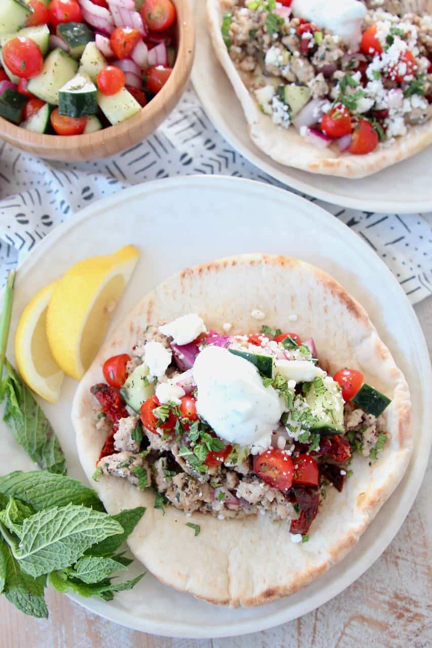 Ground turkey tacos in pita bread on plate, topped with tzatziki sauce
