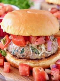 Turkey burger on bun on wood cutting board topped with diced tomatoes