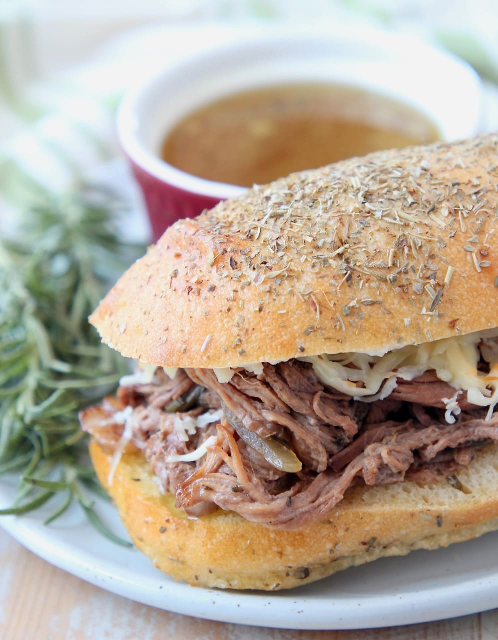 Shredded tri tip sandwich on plate with fresh rosemary