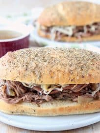 Tri tip sandwich on plate with cup of au jus and fresh rosemary
