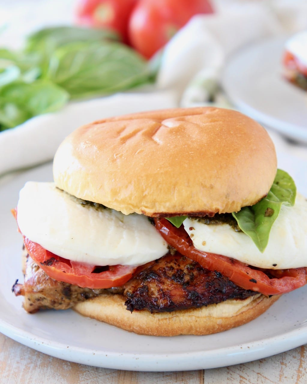 Grilled chicken sandwich with tomatoes and mozzarella cheese on white plate