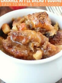 Apple bread pudding in white bowl with caramel syrup on top