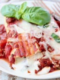Cheese manicotti on plate with marinara sauce and fresh basil