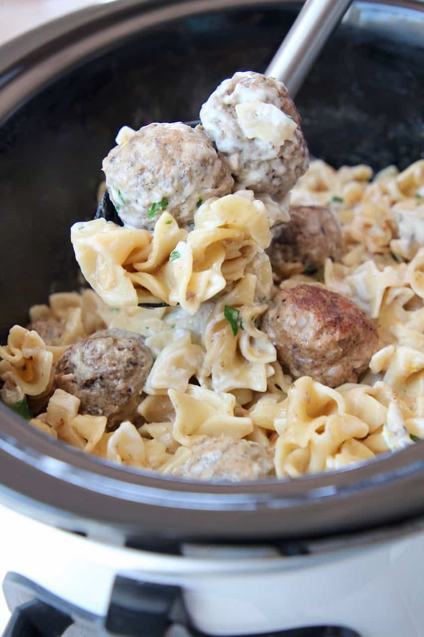 Swedish meatballs being spooned out of slow cooker