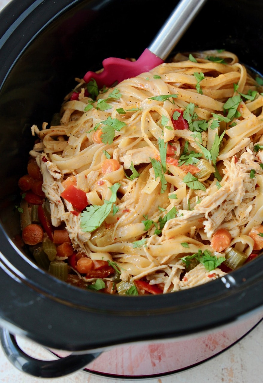 Buffalo chicken alfredo in a crock pot with carrots and red bell peppers, topped with fresh cilantro leaves, with a red spoon in the crock pot