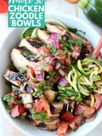 Sliced grilled chicken in bowl with tomato bruschetta and zucchini noodles