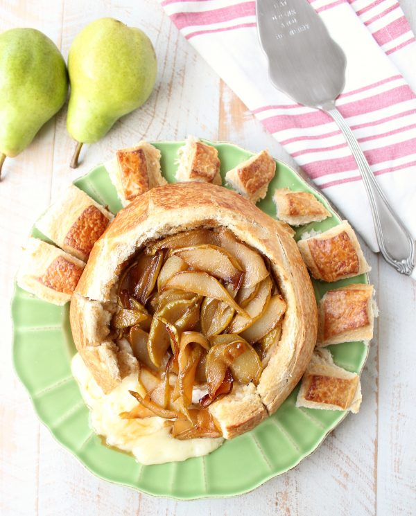 A delicious holiday party appetizer, this Baked Brie in a sourdough bread bowl is topped with buttery sweet caramelized pears and a drizzle of honey!