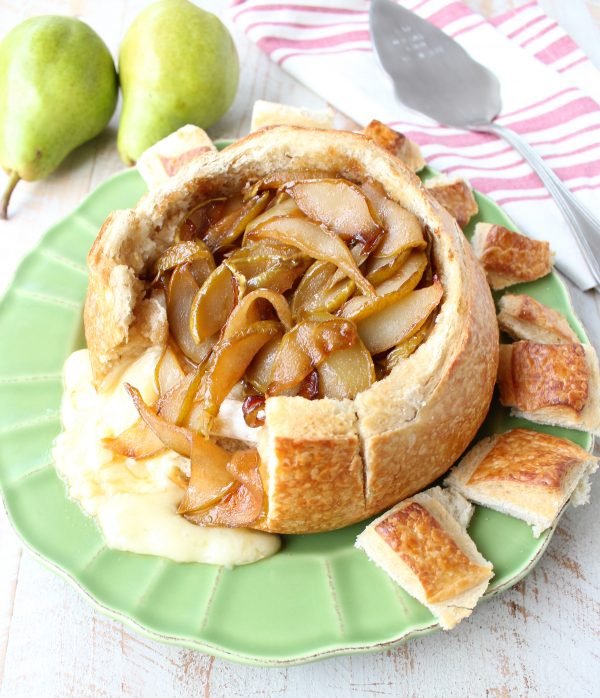 Baked brie in sourdough bread bowl with caramelized pears