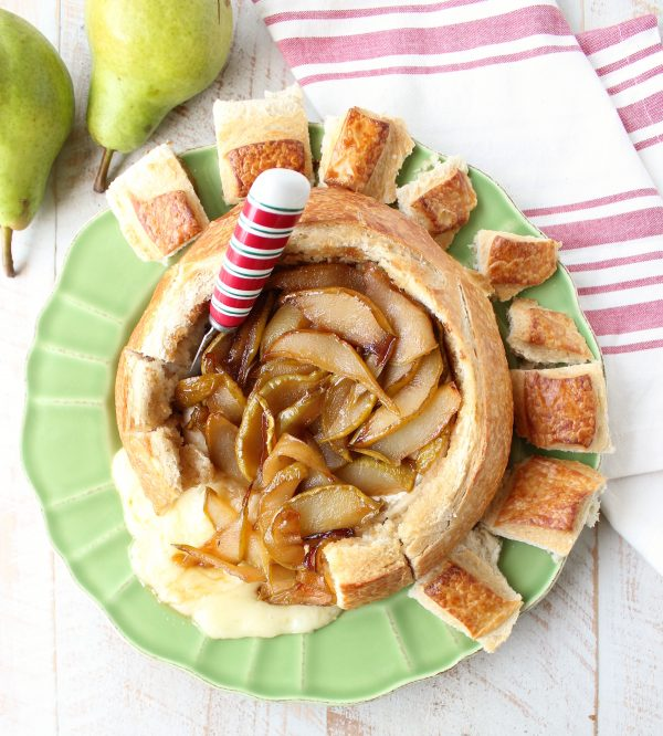 Bread bowl with baked brie, caramelized pears and red, white and green cheese spreader