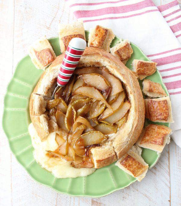 Baked brie in bread bowl with caramelized pears and honey on green plate with red and white cheese spreader and towel