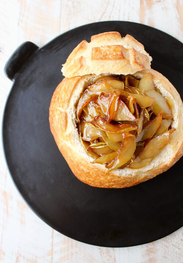 bread bowl on baking sheet filled with brie and caramelized pears