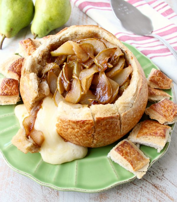 Baked brie spilling out of bread bowl onto green plate with caramelized pears on top