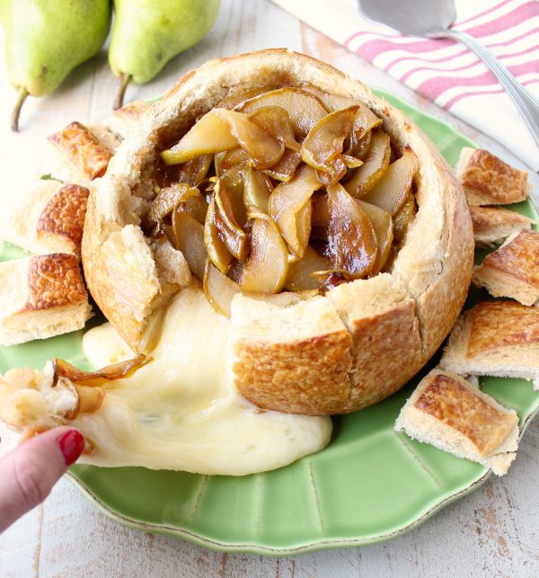 Brie cheese being pulled from a baked brie bread bowl with caramelized pears