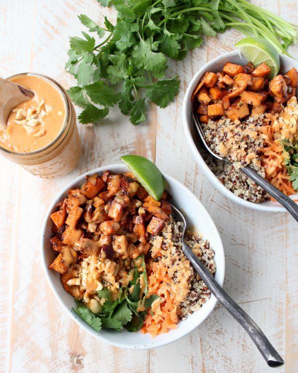 Overhead shot of Sweet Potato Buddha Bowls with a mason jar of Thai peanut sauce on the side