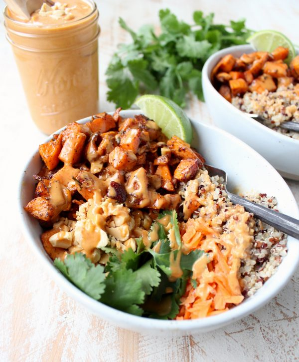 Roasted diced sweet potatoes in bowl with quinoa and thai peanut sauce