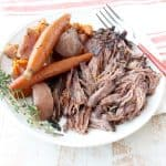 Garlic & herbs are rubbed on a beef chuck, then seared in bacon fat, placed in a crock pot & covered in red wine sauce for a tasty Slow Cooker Pot Roast!