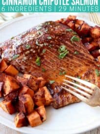 Fork cutting into glazed baked salmon on plate