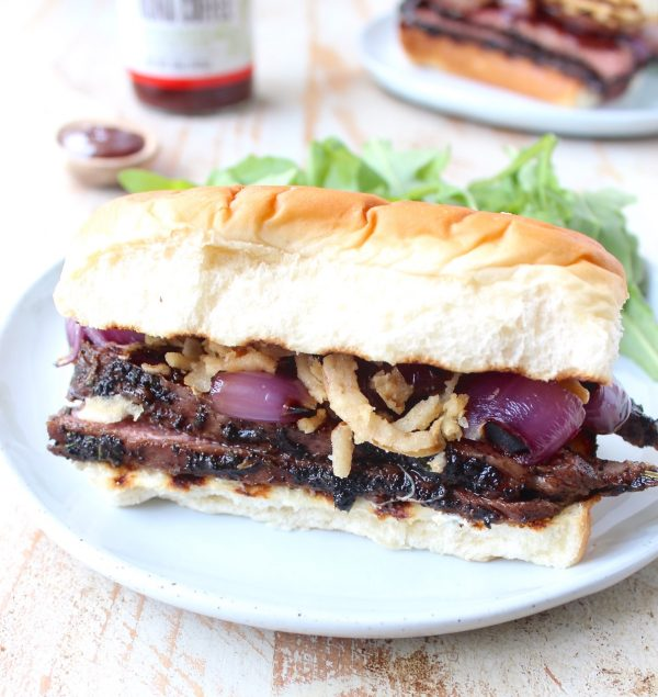 Thin slices of coffee rubbed, grilled steak are piled up with herbed goat cheese, BBQ sauce & grilled onions in this mouth-watering steak sandwich recipe!