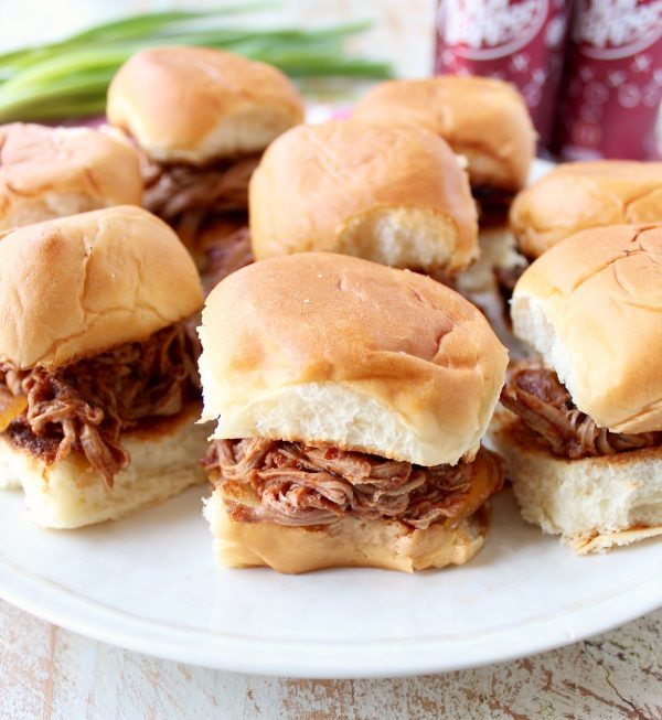 In this tasty slider recipe, pork tenderloin is covered in a delicious spice rub, slow cooked in a Dr Pepper BBQ Sauce, shredded & served on Hawaiian rolls.