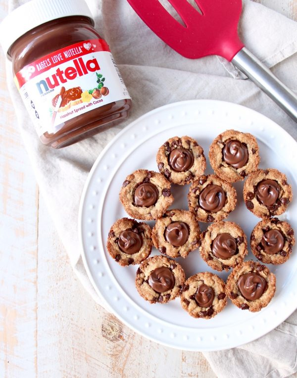 A simple chocolate chip cookie recipe is transformed into delicious chocolate chip cookie cups filled with Nutella Hazelnut Spread!