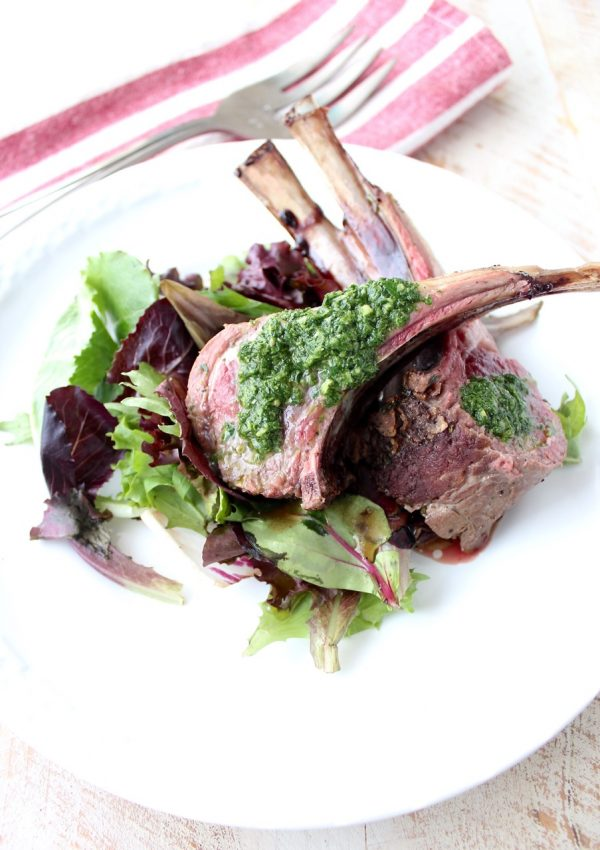 Rack of lamb is rubbed with herb butter, then roasted and topped with a mint chimichurri sauce in this elegant dinner recipe!