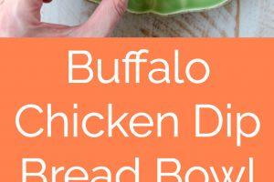 Buffalo chicken dip in sourdough bread bowl on green plate