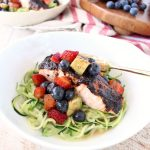Roasted balsamic salmon is served over zucchini noodles topped with a berry avocado salsa for a flavorful meal that's easy to make, gluten free, dairy free and Whole 30 approved!