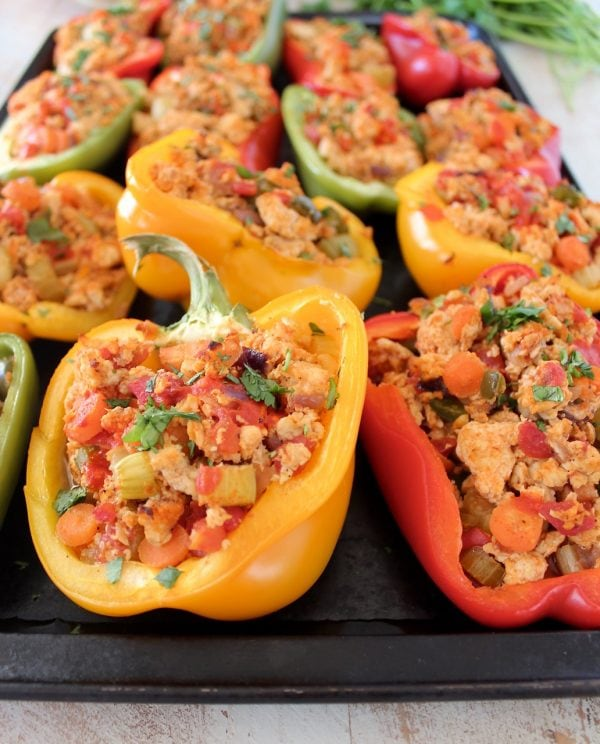 Cooked ground chicken, carrots and celery stuffed in bell pepper halves on baking sheet