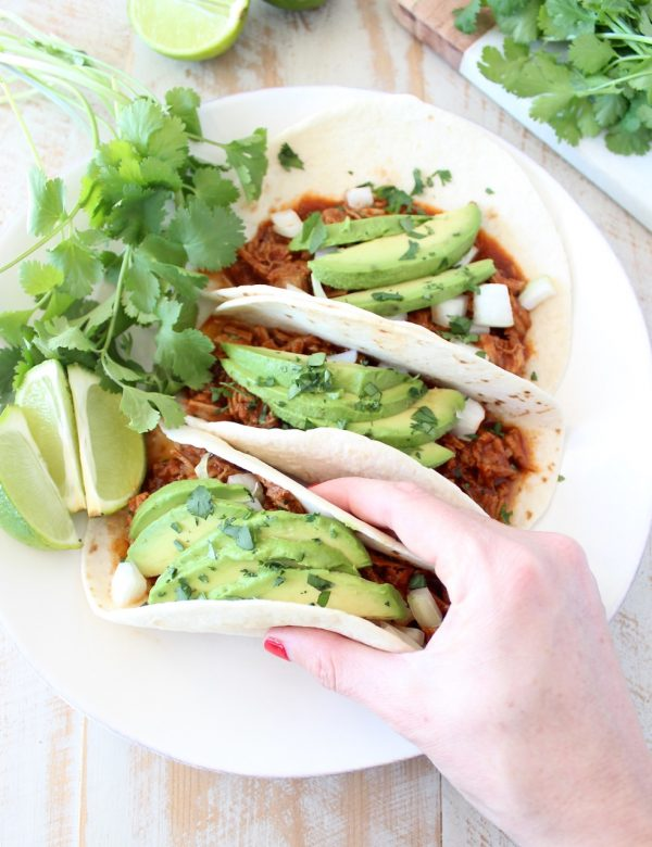 Instant pot pulled pork tacos are easy to make in under an hour with lean pork tenderloin, a delicious combination of spices and a sriracha honey tomato sauce!