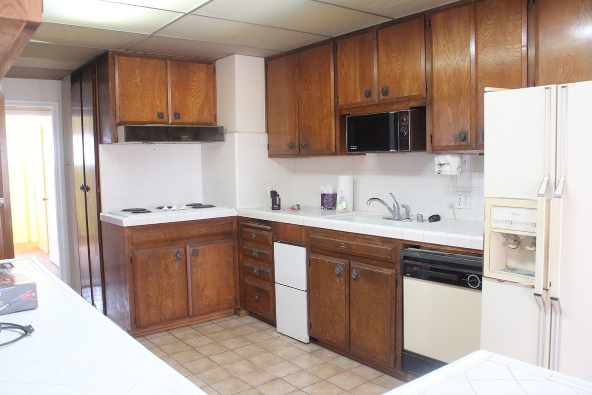 Old kitchen with brown wood cabinets and old appliances