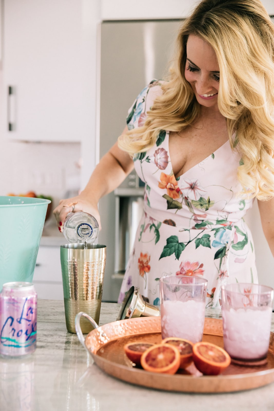 Whitney Bond making cocktails in kitchen with blood oranges, vodka and la croix