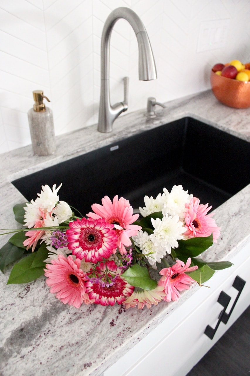 Large kitchen sink with pink and white flowers in the sink