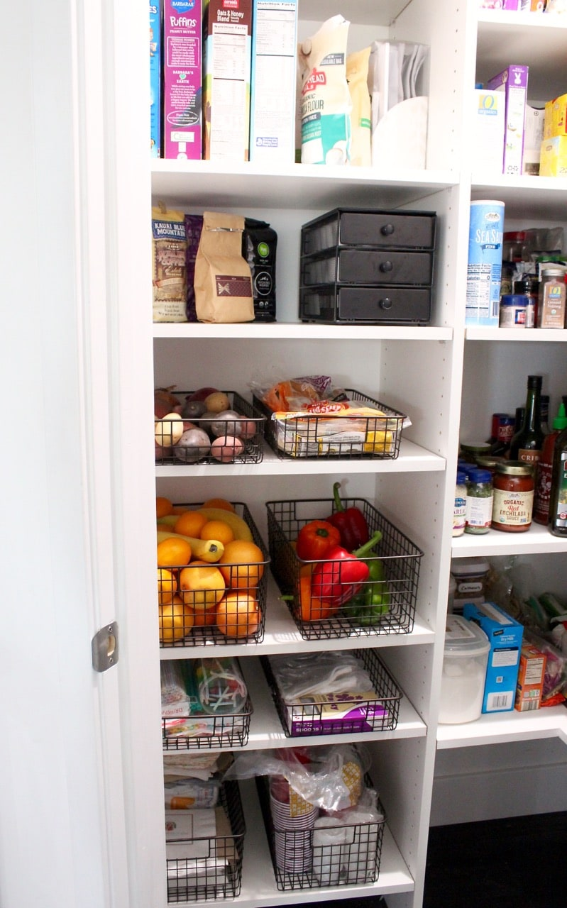 Kitchen pantry organization for fruit, veggies and plasticware.