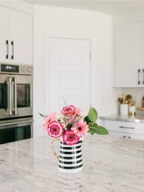 Pink flowers in black and white striped vase on kitchen island