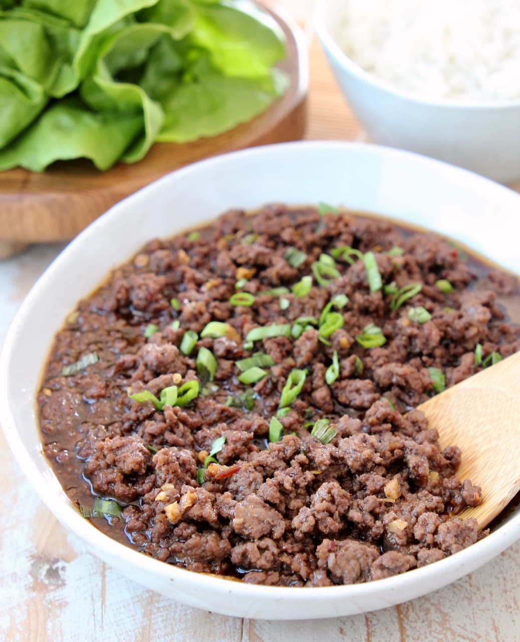 Korean BBQ Ground Beef in Bowl with Scallions and Wooden Spoon