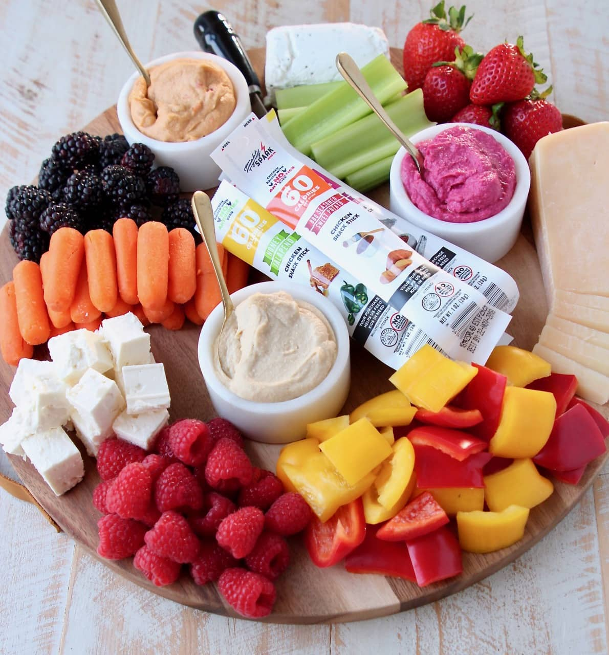 Low Calorie Charcuterie Board with Cheeses, Veggies, Berries, Hummus and Chicken Snack Sticks