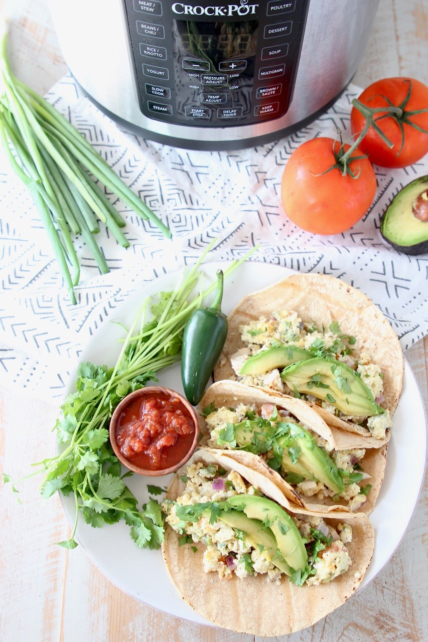 Breakfast tacos with eggs, tomatoes, avocado, jalapeno and cilantro, next to Crock Pot Pressure Cooker