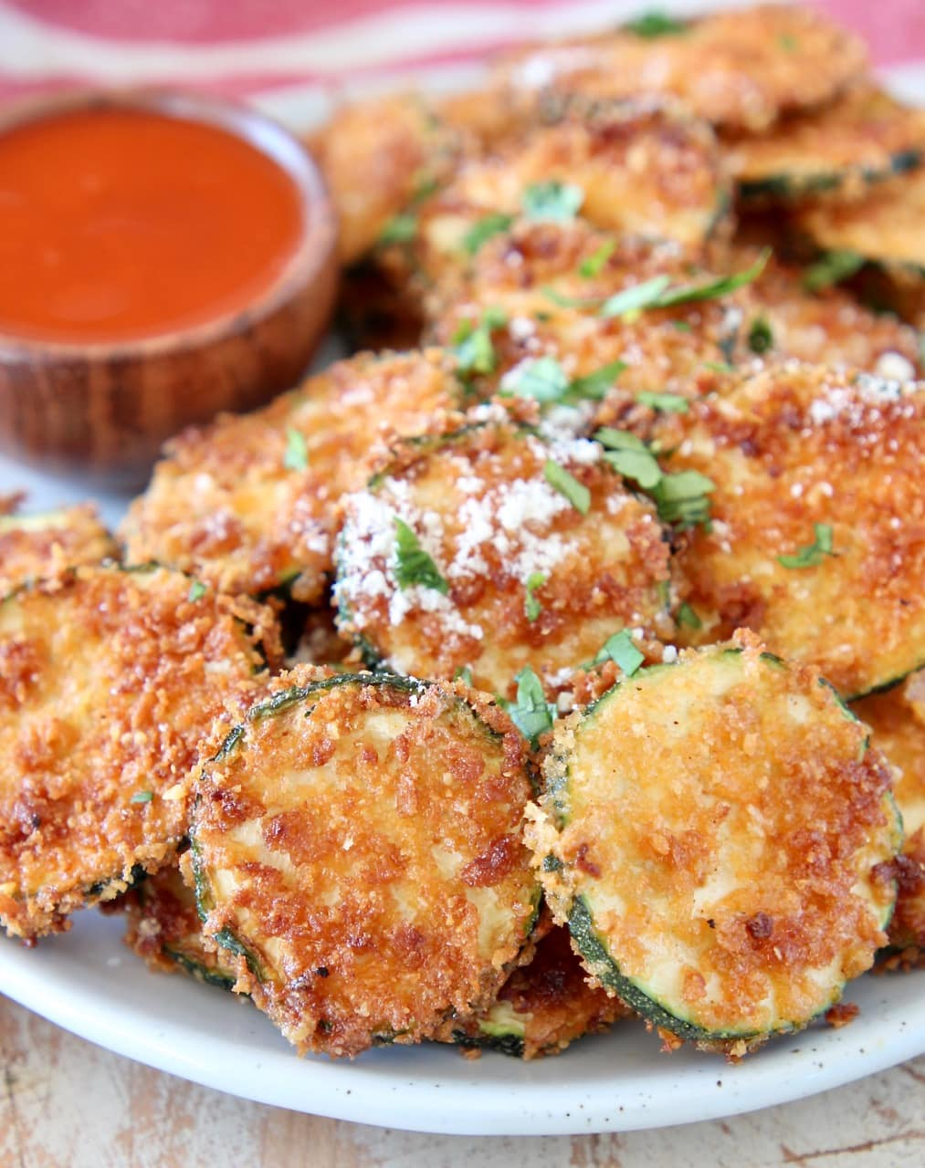 Crispy zucchini chips with parmesan cheese on plate with small bowl of buffalo sauce