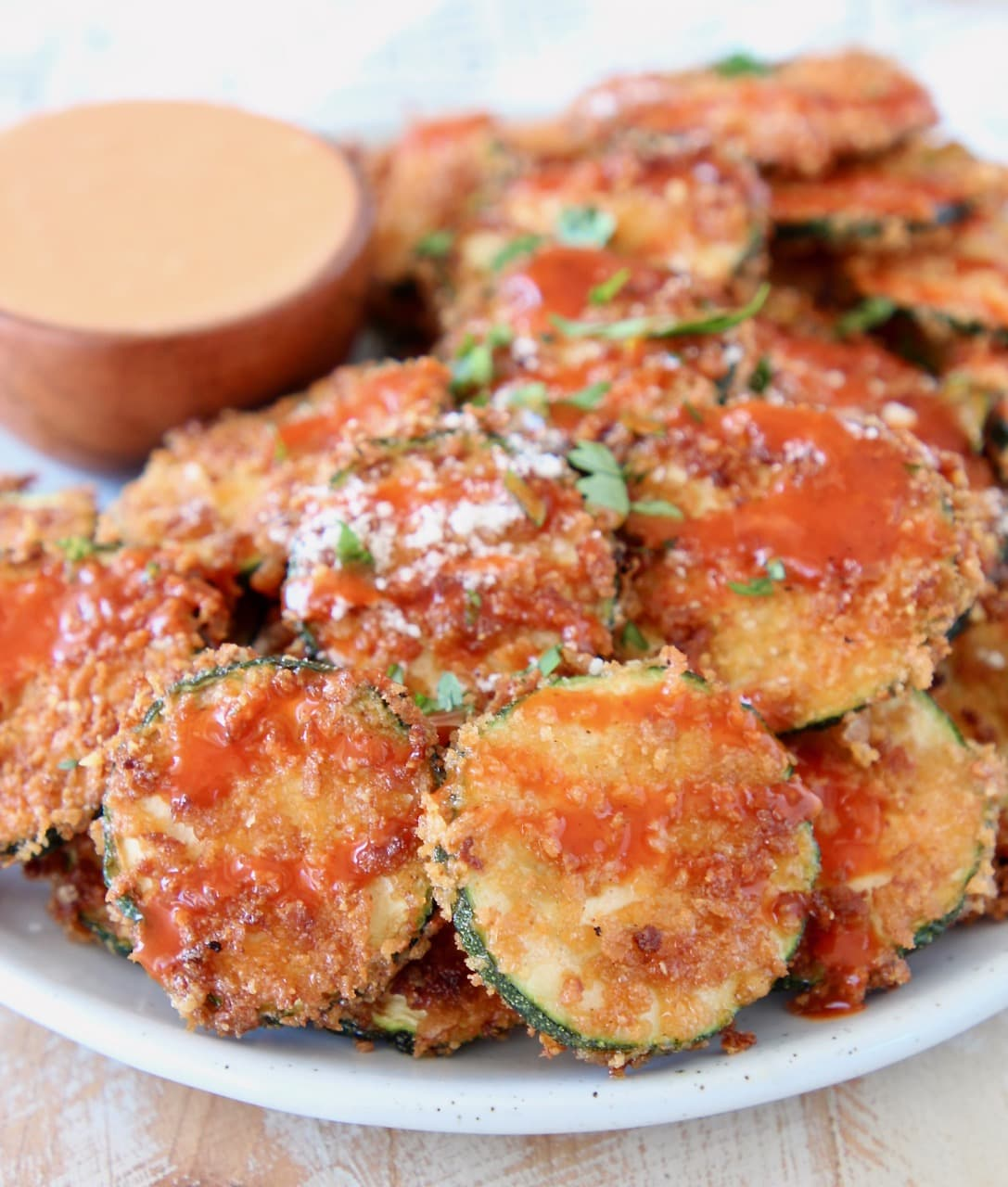 Crispy zucchini chips on plate drizzled with buffalo sauce and parmesan cheese