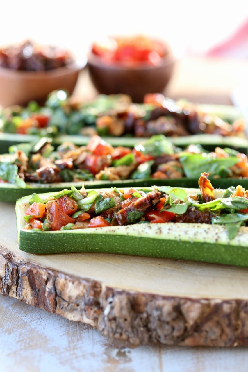 Mediterranean Tuna Salad with Roasted Red Peppers and Sun Dried Tomatoes Stuffed in Roasted Zucchini Boats on Wood Cutting Board