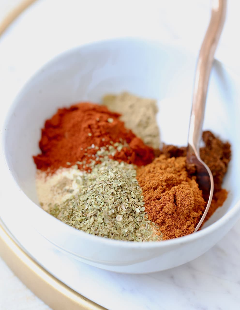 Homemade taco seasoning with 8 different spices in bowl with spoon