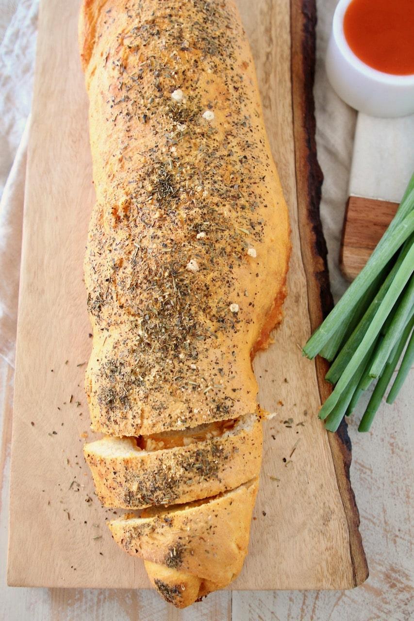 Buffalo cheesy pizza bread roll, sliced on wood cutting board with green onions