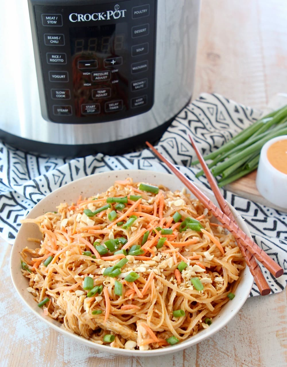 Thai peanut chicken noodles in bowl with chopsticks and Crock Pot Express Crock Multi Cooker