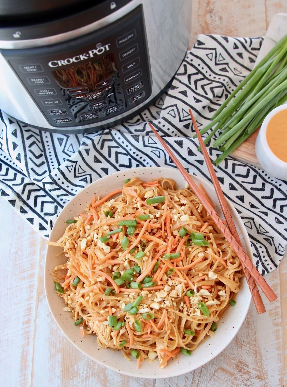 Pressure cooker chicken noodles with thai peanut sauce in bowl with chopsticks, next to Crock Pot Express Crock machine