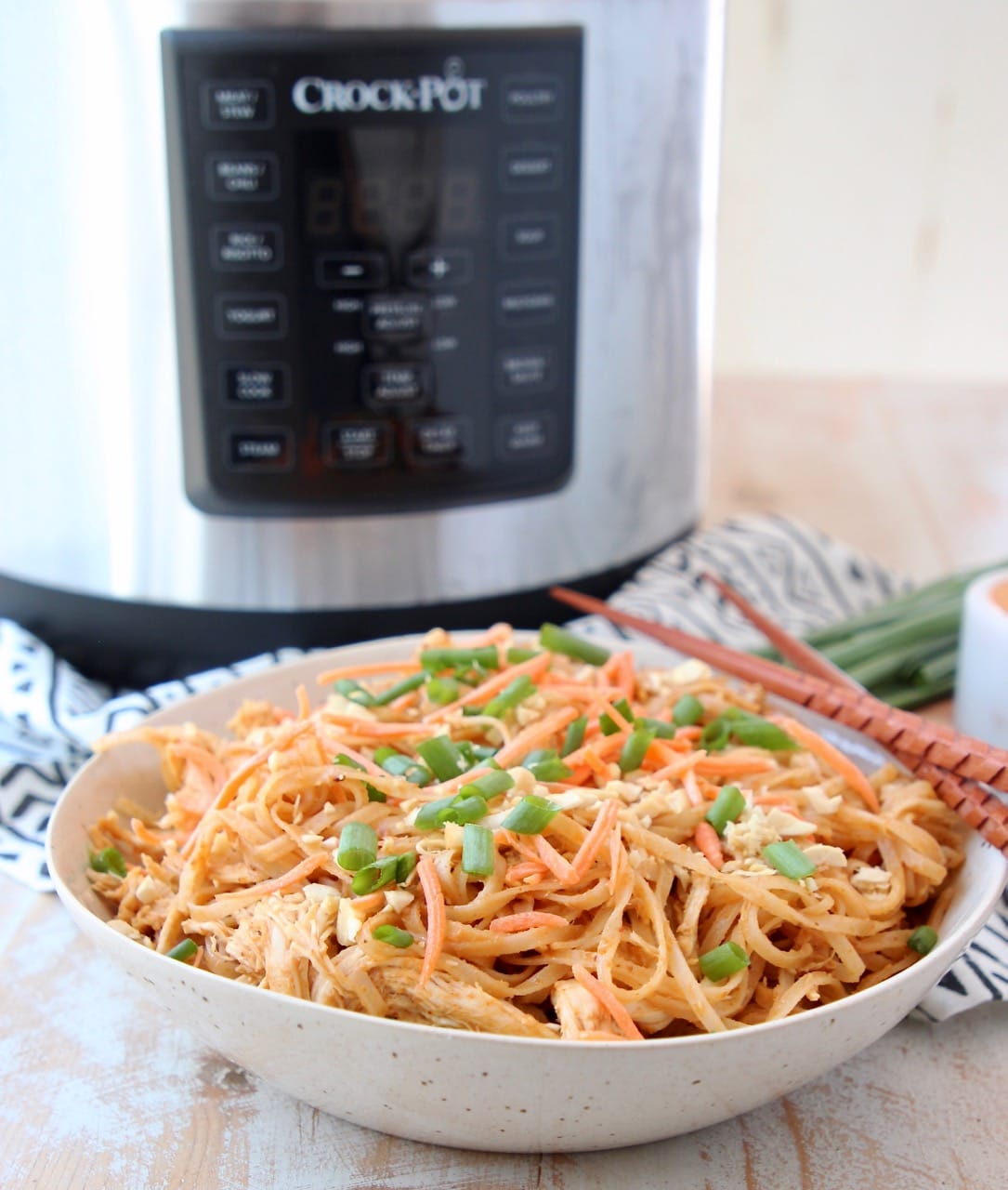 Crock Pot Express Crock Multi Cooker in background with bowl of Thai Peanut Chicken Noodles in front with chopsticks and green onions
