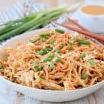 Pressure cooker chicken noodles with thai peanut sauce in bowl with diced green onions, shredded carrots and peanuts