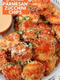 crispy zucchini chips piled up on plate drizzled with buffalo sauce